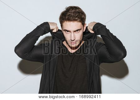 Photo of young handsome man dressed in black t-shirt and mantle standing over white background.