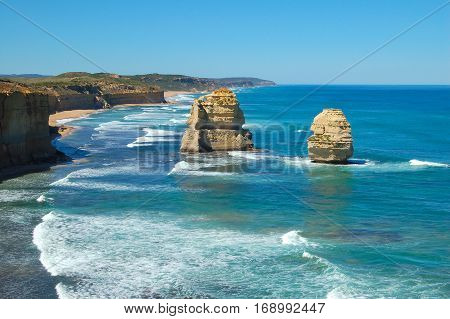 Two eroding limestone stacks standing in the blue water at the Twelve Apostles on the Great Ocean Road in Victoria, Australia