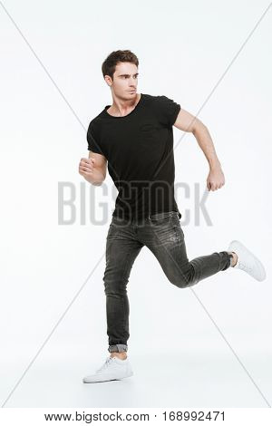 Photo of attractive young man dressed in black t-shirt running over white background looking away.