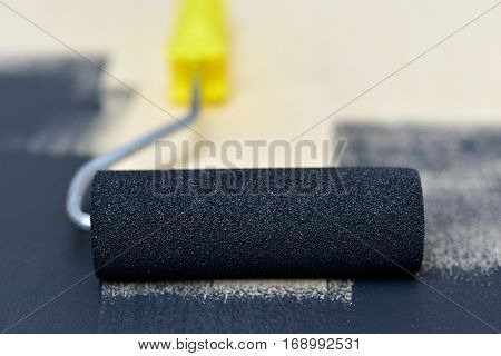 closeup of a paint roller impregnated in gray paint on a wooden board being painted with it
