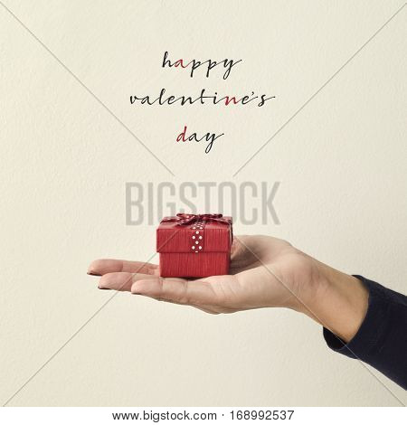 closeup of a gift in the palm of a young caucasian woman and the text happy valentines day against an off-white background