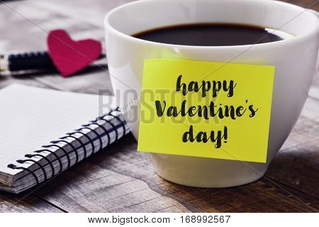 closeup of a yellow sticky note with the text happy valentines day you attached to a cup of coffee, on a rustic wooden table, next to a notebook, a red heart and a pen