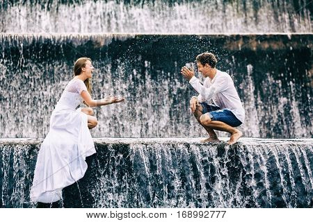 Happy family on honeymoon holidays - married loving couple splashing with fun under falling water in cascade waterfall pool. Active lifestyle people travel activity on summer vacation on Bali island.