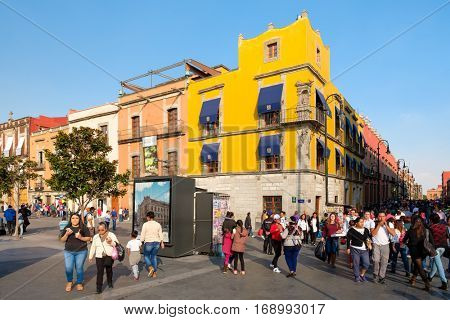 MEXICO CITY,MEXICO - DECEMBER 23,2016 : People and colorful buildings next to the Zocalo, at Mexico City Historic Center