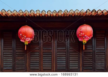 Group of traditional chinese red lanterns as decoration for China new year holidays on dark wood wall in city street. Asian arts culture travel background.
