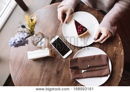 Top view picture of young woman sitting at the table in cafe and holding cake.