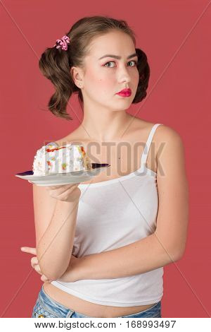 sad woman with sweet cake on red background