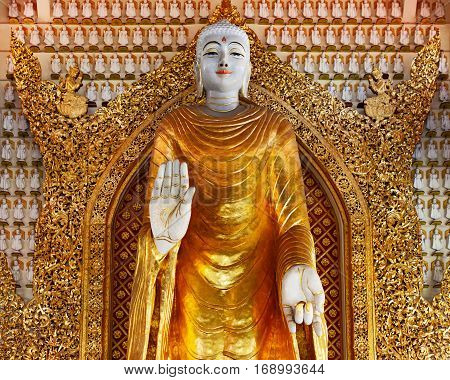 Huge gold statue of standing Buddha on 1000 Buddha wall background. Interior of ancient Burmese buddhist temple Dhammikarama in Georgetown on Penang island. Asian arts culture. Travel background.