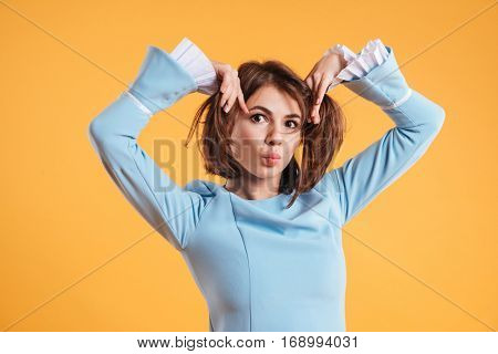 Playful comical young woman joking and making funny face over yellow background