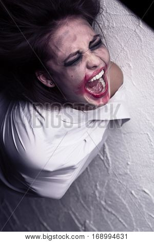 screaming crazy woman with smeared makeup in straitjacket