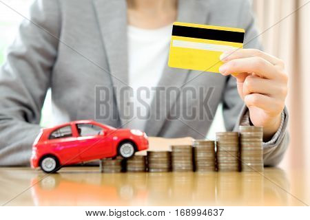 Businesswoman hand hold credit card a toy car and a stack of coins