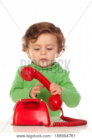 Baby with one years old playing with a red phone isolated on a white background