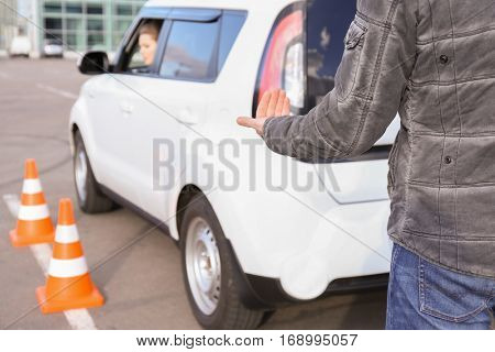Instructor and woman passing driving license exam outdoors