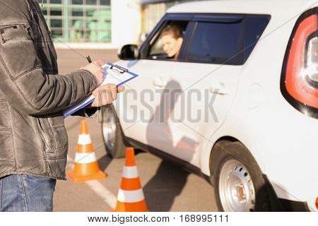 Instructor in driving school writing down results of exam