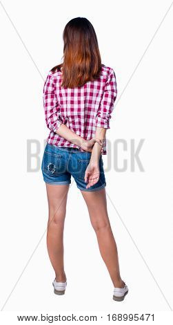 back view of standing young beautiful  woman.  girl  watching. Rear view people collection.  backside view of person.  Girl in shorts and a plaid shirt, clasped his hands behind his back.