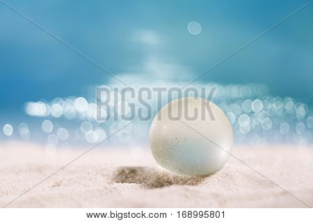 sea glass ball seaglass on  sand with ocean , beach and patches of sunlight, shallow dof