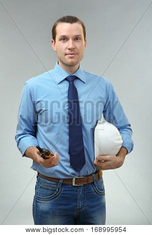 Handsome engineer with portable radio transmitter on light background