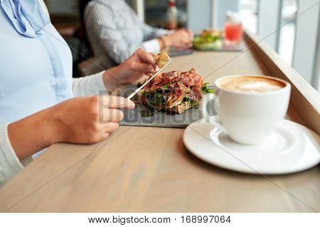 food, dinner and people concept - woman eating prosciutto ham salad on stone plate at restaurant and coffee cup on table