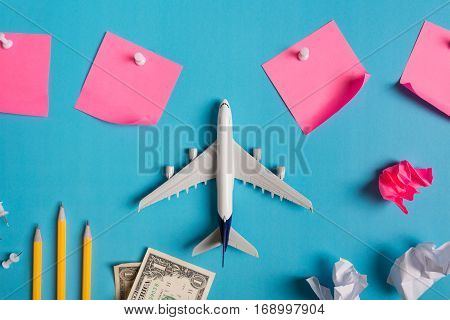 Preparation for Traveling concept paper noted airplane money passport pencils paper ball push pin on blue background with copy space.