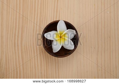 frangipani in bowl on wooden