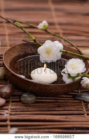 cherry flower in wooden bowl with stones, candle and mat