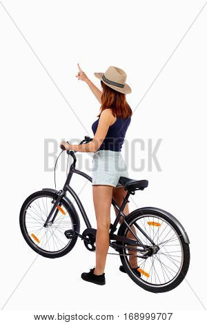 back view of pointing woman with a bicycle. cyclist sits on bike. Rear view people collection. backside view of person. Isolated over white background. Girl cyclist in summer clothes shows thumb up