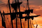 all ship masts and rigging silhouetted against a dramatic sky at sunset poster