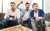 Interesting entertainment. Nice good looking young men holding game consoles and playing video games while having fun together poster