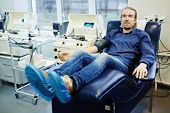 Donor of blood sitting in armchair by platelets blood separation machine poster