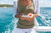 Tourist using smartphone mobile app to text sms while traveling on cruise ship tour. Woman holding phone texting on boat ride during travel summer vacation. poster