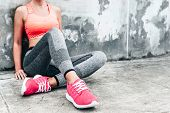 Fitness sport woman in fashion sportswear doing yoga fitness exercise in the city street over gray concrete background. Outdoor sports clothing and shoes, urban style. Sneakers closeup. poster