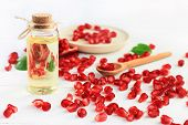 Bottle of pomegranate oil. Natural body care products. Clusters of juicy red seeds scattered white table. poster