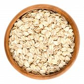 Oatmeal, rolled oats in wooden bowl. Dehusked, hulled oats, rolled into large whole flakes. Porridge oats, used in granola or muesli. Isolated macro food photo close up from above on white background. poster