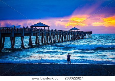 Sunrise over the Juno Beach, Florida fishing pier as visitors fish from above and on the beach.