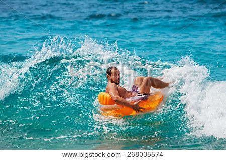 Excited Bearded Hipster In Inflatable Ring Have Fun In Beach Surf. Funny Man Riding On Tubing In Bre