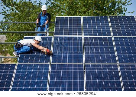 Two Technicians Working With Electrical Screwdriver Connecting Shiny Solar Photo Voltaic Panel To Me