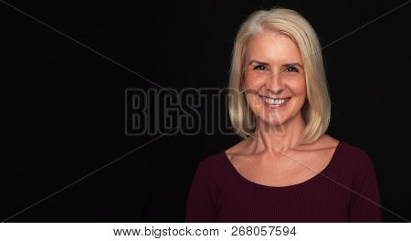 Happy Senior Woman Is Smiling Toothy. Black Background