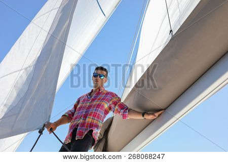 Handsome man with sunglasses is on yacht and keeps sail in blue sea at summer day, under view