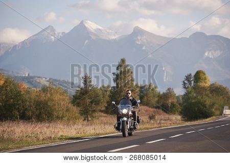 Bearded Motorcyclist In Sunglasses And Black Leather Clothing Riding Cruiser High-speed Motorbike On