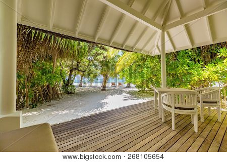 Luxurious Beach Villa With Chairs And Wooden Deck In The Tropical Island Near Blue Lagoon Of Maldive