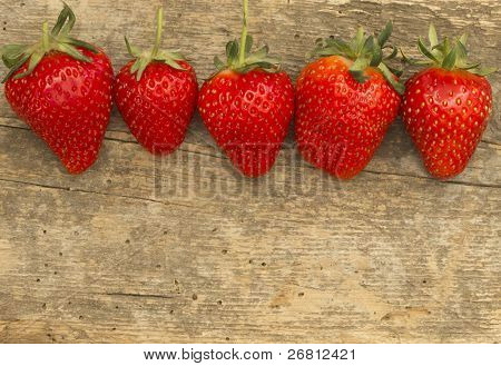 strawberries in the line on the wooden background