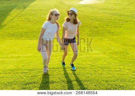 Two Teen Girls Hold Hands On The Green Grass In The Park On A Hot Summer Day At The Golden Hour. Fri