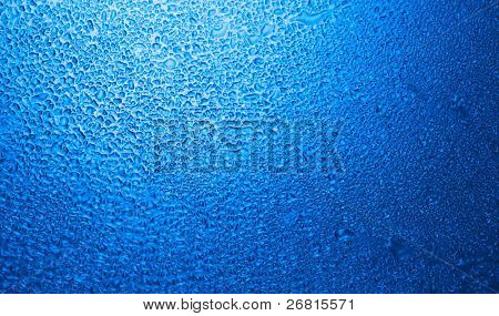 Wet glass with water drops in blue tone
