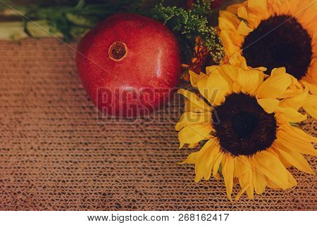 A Pair Of Sunflowers And A Pomegranate Fruit, Arranged On A Light Brown Textured Background