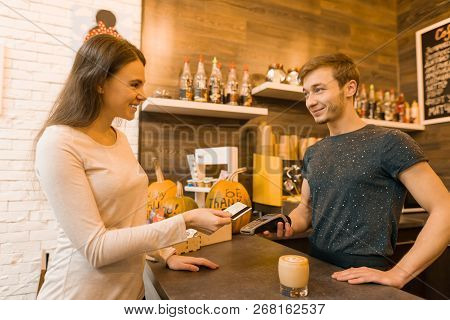 Girl Coffee Shop Client Pays Coffee By Credit Card, Barista Holding A Credit Card Reader Machine.