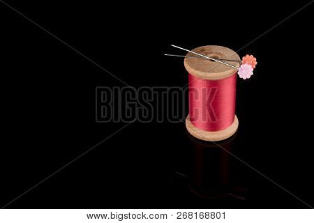 Pink Thread With Two Needles On Top In Flower Shape, Cerise Pink, Wooden Bobbin Isolated On Black Ba