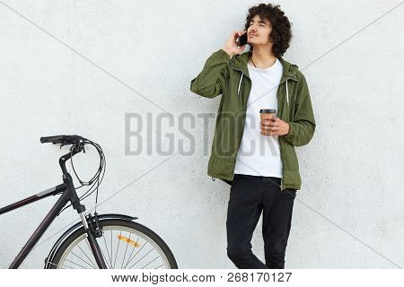 Shot Of Concentrated Male Youngster Speaks Via Cell Phone With Girlfriend, Tells About His Bike Trav