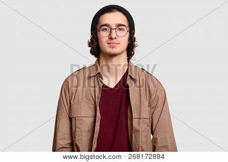 Photo Of Curly Male Teenager Wears Round Optical Spectacles, Black Hat, Casual Shirt, Looks Directly