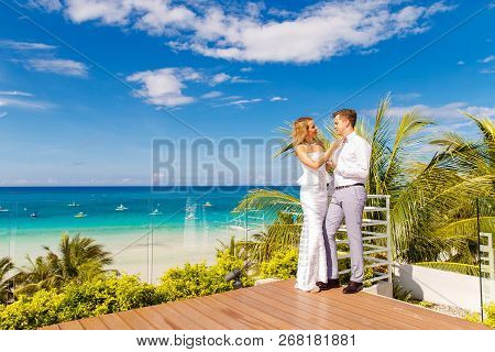 Beautiful Blonde Bride In White Wedding Dress And The Groom On The Roof Of The Hotel. Tropical Sea A
