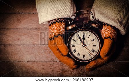 Hands In Mittens Holding An Alarm Clock With Bell Wooden Table. Above View